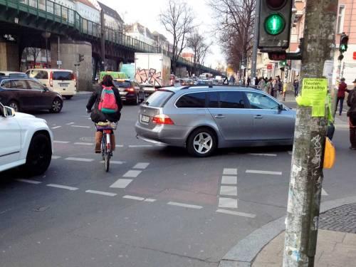Eine Kreuzung in Berlin. Der Fahrer des silberfarbenes Autos ist halb abgebogen und blockiert die Radspur. Radler können nicht durchfahren, und mussen warten, oder hinten ausweichen.